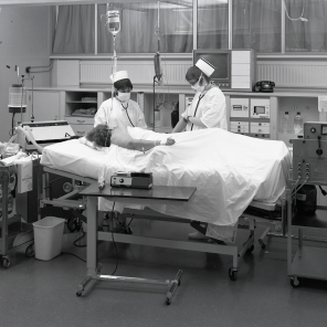 2016_107_025a Two nurses at a patient's bedside and typical monitoring equipment, 1970