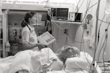 Critical Care nurse, Lily Foubert, checks a patient's vital signs using the Electronic Patient Information Chart, 1990.