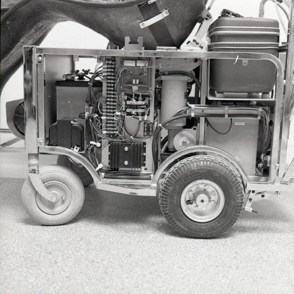 Detail on Kevin Keough's chair. An automatic switching and dual charger controls for the respirator are in the centre; the portable respirator is on top at the back; the motor to drive the chair is the white cylinder under the seat; and there are two batteries at the front and rear of the chair.