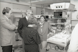 Nurse Debra Armitage explaining the functionality of radiant warmer beds with overhead heater-unit, 1986.