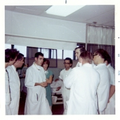 Dr. Bryan Kirk with residents in ICU. Others in photo: DeSnigurowicz, Dr. Kassir, Averill Winestock, Mr. Malaviya, Dr. Bristovo(?), Dr. Pavlin, Dr Flett (with back to camera). October/November 1969.