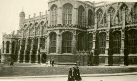 [Unidentified building with three nursing sisters walking by, England]