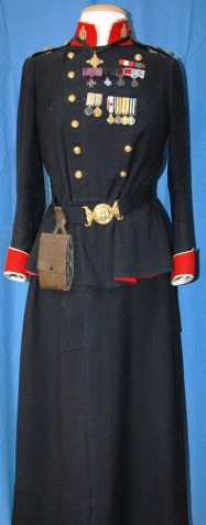 "Alfreda Attrill's navy blue military uniform with 2 Canadian Medical Corps Officer collar pins, 11 round brass Canadian Medical Corps buttons, 2 brass pins shaped to form ""1 Canada"", 4 brass shoulder pins encircled by golden leaves with a hint of red and turquoise in raised centre, and Felt belt with brass buckle depicting British coat of arms"