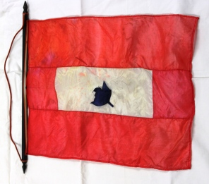 [Red silk flag with white centre and a black hand-cut leaf pinned to centre.]