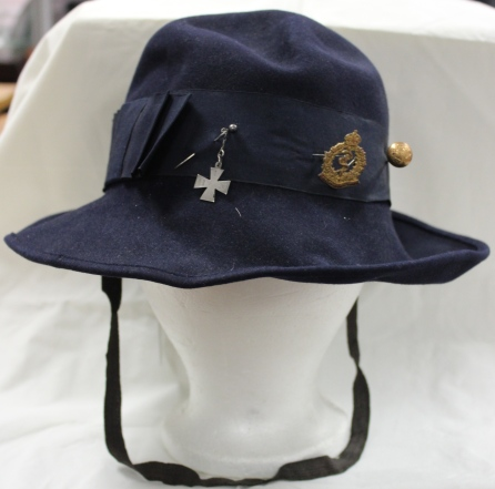 [Navy blue felt hat that belonged to Ada J. Ross. Includes brass hat pin, HIN Cross and Canadian Medical Corps pin.