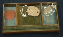 Wooden lined tray containing Ruby Dickie's Queen Alexandra's Imperial Military Nursing Service Rerserve identification tags.