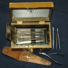 Brown wooden box with green silk lining. Includes key to outside lock. Contains brown leather nurse's chatelaine that includes tweezers, scissors and thermometer.