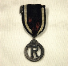 [Queen Alexandra's Imperial Military Nursing Service Reserve badge belonging to Ruby Dickie.]