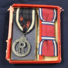 Queen Alexandra's Imperial Military Nursing Service Reserve badge and ribbon belonging to Ruby Dickie.