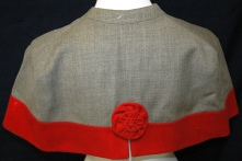 Queen Alexandra's Imperial Military Nursing Service Reserve Cape belonging to Ruby Dickie. [Capes of reserve QAIMNS members with gray with a red border. The scarlet Alexandra rose was embroidered on the back of the cape.]