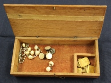 Wooden jewelry that belonged to Ruby Dickie. Box has hook enclosure and contains round pearl buttons and flat white buttons, Egyptian currency including 3 Drams and 5 Scruples.