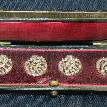 Wooden box with red lining that belonged to Ruby Dickie. Contains five silver J.D.W.D. detachable buttons.