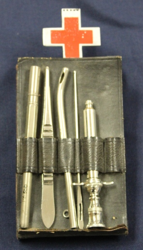 [Ada J. Ross Chatelaine.] Black leather case hung from a Red Cross belt clip containing a broken thermometer, tissue forceps, probe, metal suction tip, and a metal hypodermic syringe.