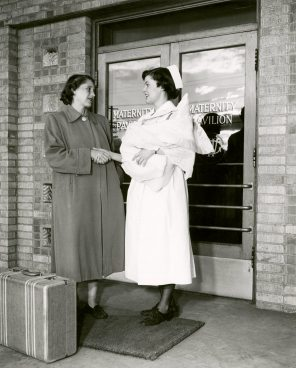 Betty Bramble '53 escorting new mother and babe to door at Women's Pavilion circa 1952. HSC Archives/Museum 998.11.18 F4_P2_023