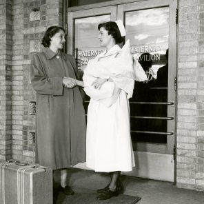 Betty Bramble '83 escorting new mother and babe to door at Women's Pavilion circa 1952. HSC Archives/Museum 998.11.18 F4_P2_023