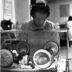 Nurse with newborn in an incubator, ca. 1970s