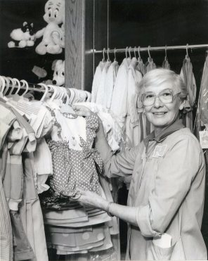 Baby clothes in the White Cross Guild gift shop held by volunteer coordinator. HSC Archives/Museum White Cross Guild Collection